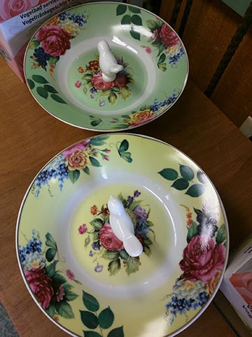 Ceramic floral plates with a ceramic bird standing in the center